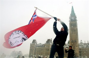 A First Nations member waves a flag as he takes part in a protest on Parliament Hill in Ottawa on Friday, December 21, 2012. THE CANADIAN PRESS/Fred Chartrand