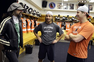 In this Tuesday, Feb. 5, 2013 photo provided by the Philadelphia Flyers, filmmaker Rob Zombie, left, visits with Flyers' Maxime Talbot, center, and Claude Giroux in their locker room before an NHL hockey game against the Tampa Bay Lightning in Philadelphia. Zombie has moved from horror to hockey. His next project has nothing to do with shock rock or slasher flicks. He's working on a movie on the old Philadelphia Flyers' Broad Street Bullies teams of the 1970s. (AP Photo/Philadelphia Flyers, Zack Hill)