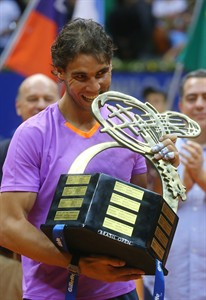 Spain's Rafael Nadal bites the Brazil Open ATP tennis tournament trophy as he poses for pictures after defeating Argentina's David Nalbandian in the final match in Sao Paulo, Brazil, Sunday, Feb. 17, 2013. Nadal won 6-2, 6-3. (AP Photo/Andre Penner)
