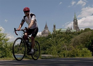 A cyclist rides with a helmet near Parliament Hill on July 8, 2010. THE CANADIAN PRESS/Adrian Wyld