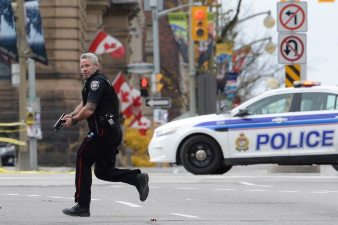 An Ottawa police officer runs with his weapon drawn after a shooting in Ottawa on Oct. 22, 2014. THE CANADIAN PRESS/Sean Kilpatrick