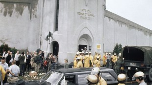FILE - In this Sept. 13, 1971 file photo, prison guards and New York State troopers gather outside Attica State Prison as they prepare to enter the prison and retake it after inmates rioted and held the prison for five days, in Attica, N.Y. More than 40 years after the nation's bloodiest prison rebellion, newly released documents contain accounts, some never before seen publicly, from National Guardsmen and a doctor who said they saw injured inmates beaten with clubs and others with wounds indicating they were tortured as state police and guards retook control. (AP Photo, File)