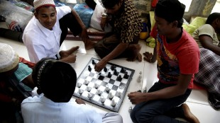 Migrants play chess at a temporary shelter in Lhoksukon, Aceh province, Indonesia, Thursday, May 21, 2015. In the past three weeks some thousands of people, mainly Rohingya Muslims fleeing persecution in Myanmar and Bangladeshis trying to escape poverty, have landed in overcrowded boats on the shores of Indonesia, Malaysia and Thailand. After initially pushing many boats back, Malaysia and Indonesia announced on Wednesday that they will offer temporary shelter to incoming migrants. (AP Photo/Tatan Syuflana)