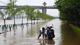 In this Thursday, May 21, 2015 photo released by China's Xinhua News Agency, a resident cleans a motorcycle on a flooded road in Liuzhou, southwest China's Guangxi Zhuang Autonomous Region. The death toll in China's latest round of flooding has risen to more than 50, including two schoolchildren aboard a bus carrying more than twice its authorized passenger load that plunged into a pond, authorities said Saturday. (Li Bin/Xinhua via AP) NO SALES