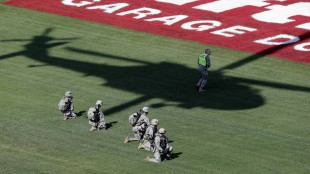 An Army repel team kneels in the infield while a helicopter hovers above during a demonstration prior to the NASCAR Sprint Cup series auto race at Charlotte Motor Speedway, Sunday, May 24, 2015, in Concord, N.C. (AP Photo/Gerry Broome)
