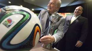 "FIFA President Sepp Blatter, left, pretends to shine the trophy with his suit jacket sleeve while posing for photographs with Canadian Soccer Association President Victor Montagliani following the opening press conference for the FIFA Women's Under 20 World Cup in Toronto, Ontario on Monday, Aug. 4, 2014. Montagliani has been named to a special CONCACAF committee charged with ""evaluating and sustaining"" all of the confederation's business operations of the wake of FIFA's mushrooming corruption scandal. THE CANADIAN PRESS/Peter Power"