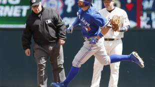 Toronto Blue Jays' Kevin Pillar, center, runs past Minnesota Twins second baseman Brian Dozier and second base umpire Eric Cooper, left, as he rounds the bases after hitting a solo home run off Twins pitcher Kyle Gibson in the fourth inning of a baseball game, Saturday, May 30, 2015, in Minneapolis. (AP Photo/Jim Mone)